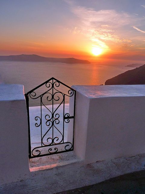 Gate at sunset.  Iron gate overlooking the sea at sunset. Fira. Santorini island, Cyclades islands, Greece