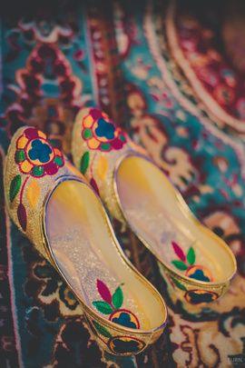 Wedding Shoes - Golden Wedding Juttis with Multi-Colored Thread Work | WedMeGood | Picture Courtesy: Burn Pixels Photography #wedmegood #juttis #multicolored # gold