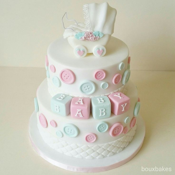 Pink, blue and white baby shower cake topped with handmade pram /stroller