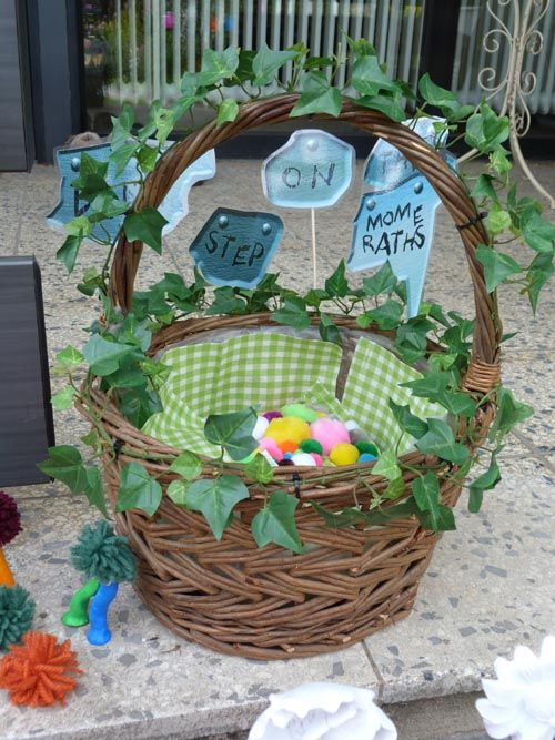 """Basket with food and """"Don't step on the mome raths"""" signs. The mome raths are represented with fluffy balls, glued on a paper napkin in the shape of an arrow."""