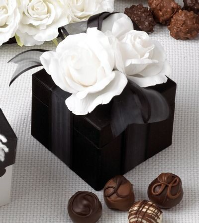 mini versions of this on tables with favors would be really cute. purchase a bunch of black and white boxes-- wrap them up with paper flowers on top :)