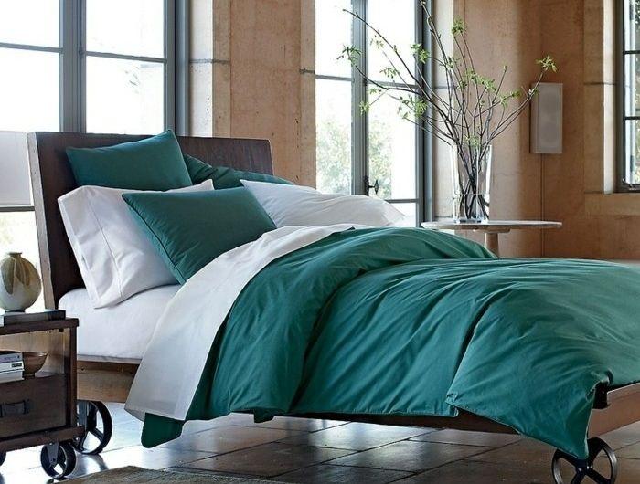 exemple-deco-bleu-canard-linge-maison-et-taies-d-oreillers-couleur-bleu-canard-revetement-murs-en-bois-lit-à-roulettes-vintage-et-tale-de-nuit-vintage-industrielle