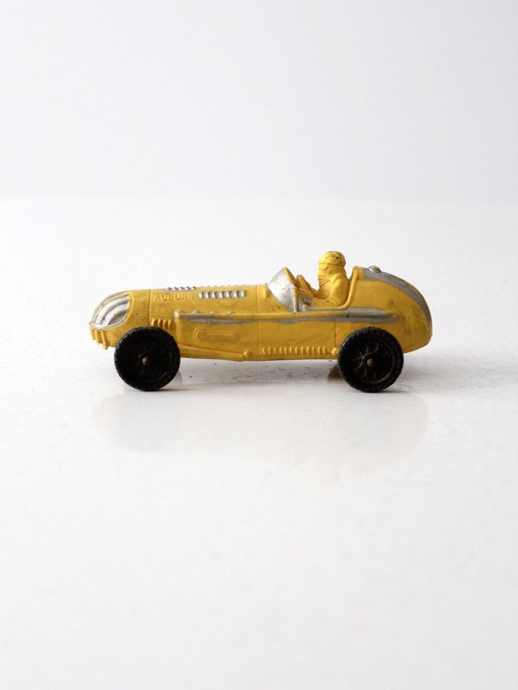 A vintage Auburn Rubber Company toy car circa 1960. The yellow Indy style racer features metallic silver detailing and black wheels. - Auburn Rubber Company - vinyl toy car - open race car style - yel