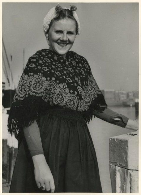 Scheveningse vrouw aan de tweede haven; zij draagt een geplooide kanten muts, een ijzer met gouden boeken, een Turkse omslagdoek. 1954 WF van Heemskerck-Düker #ZuidHolland #Scheveningen