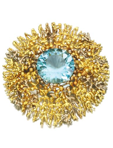 GOLD AND AQUAMARINE BROOCH, STUART DEVLIN, CIRCA 1970 Set with a circular-cut aquamarine to a mount composed of layered figures, maker's mark for Stuart Devlin, British hallmarks for London, 1971.