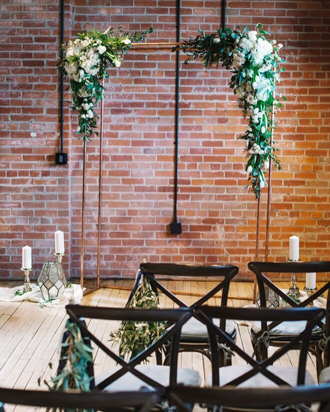 Calgary urban industrial wedding at Charbar with a copper arbour and lush white & green arbour floral arrangements!  Photo: @corrinawalker   Calgary Wedding Florist- Flowers by Janie  www.flowersbyjanie.com