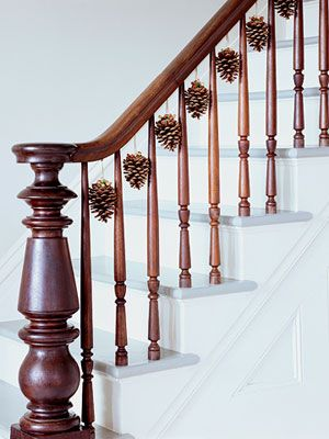 Pinecones hanging from banister. Simple and natural and awesome Christmas decor.