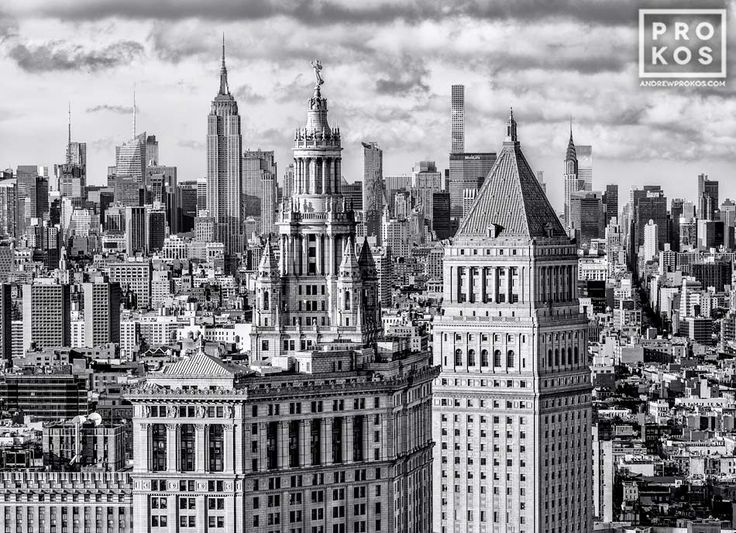 A black and white view of the Municipal Building and 40 Centre Street in the foreground, with the skyscrapers of Midtown Manhattan and the Empire State Building in the distance, New York City