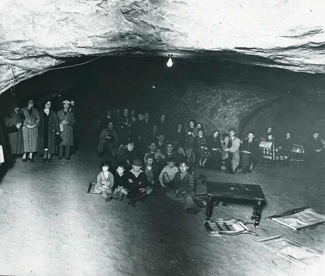 """St Clements Caves in Hastings (Sussex) formed a natural air-raid shelter for many Old Town families when bombing began in 1940. The caves were kitted out with 500 bunk beds. The people ate, slept and generally lived as an underground community. A fully equipped medical centre, sick bay and dining hall were also added and an official inspector from the Civil Defence Commissioner remarked that it was """"the best air-raid shelter in the country""""."""