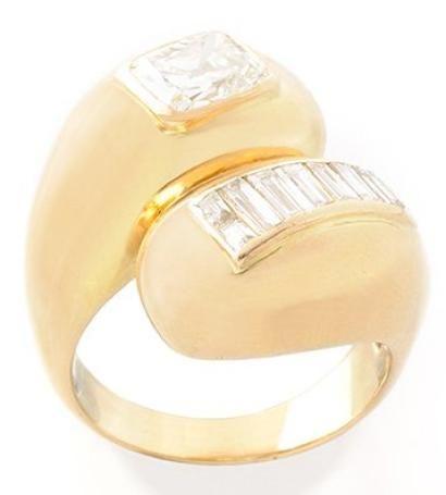BAGUE en or jaune stylisant le «yin et yang» ornée d 'un diamant de taille coussin et d'une succession de huit diamants taille baguette par Suzanne Belperron en 1968. Accident sur un diamant de taille baguette. Poids brut: 20,6 g. TDD: 61 Accompagnée de son certificat d' origine d'Olivier Baroin.