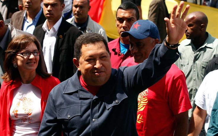 Hugo Chávez, saluda a la gente que se encuentra fuera del lugar de votación.- AP