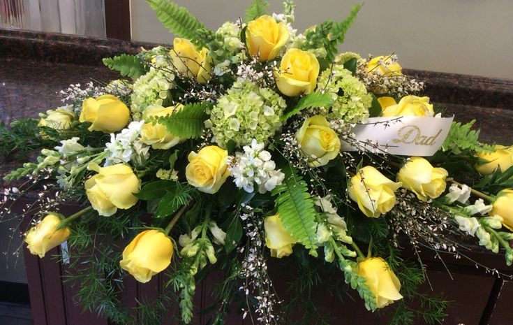 Yellow green and white casket spray