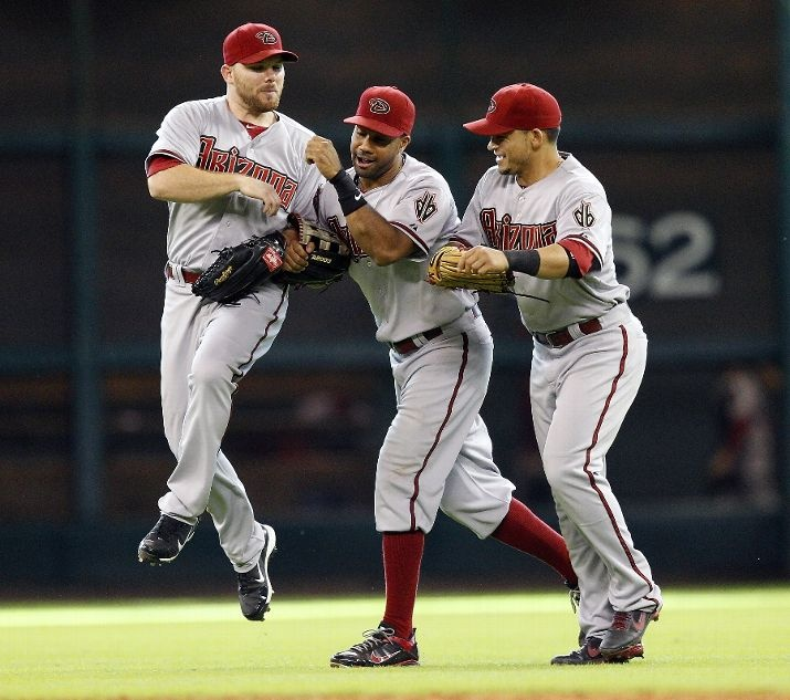 Jason Kubel #13, Chris Young #24 and Gerardo Parra #8 of the Arizona Diamondbacks celebrate after the final out against the Houston Astros at Minute Maid Park on August 19, 2012 i