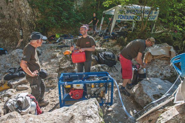 """la fontaine de Vaucluse  :                         Camp de base Le """"projet 360"""" a mobilisé douze bénévoles. Ici, l'équipe utilise un compresseur pour le gonflage des bouteilles de plongée. La fabrication des mélanges respiratoires pour les différentes profondeurs prend plusieurs heures."""