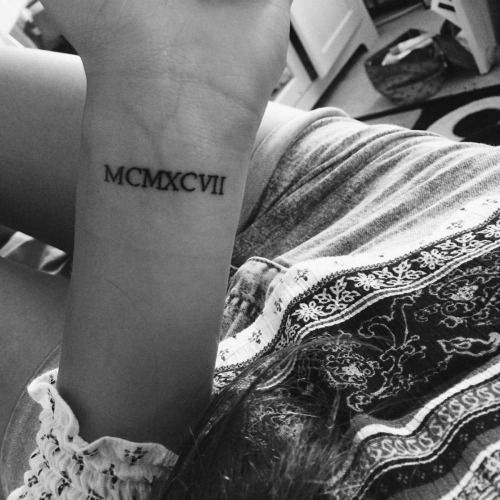 1997 in roman numerals on Ginas wrist.