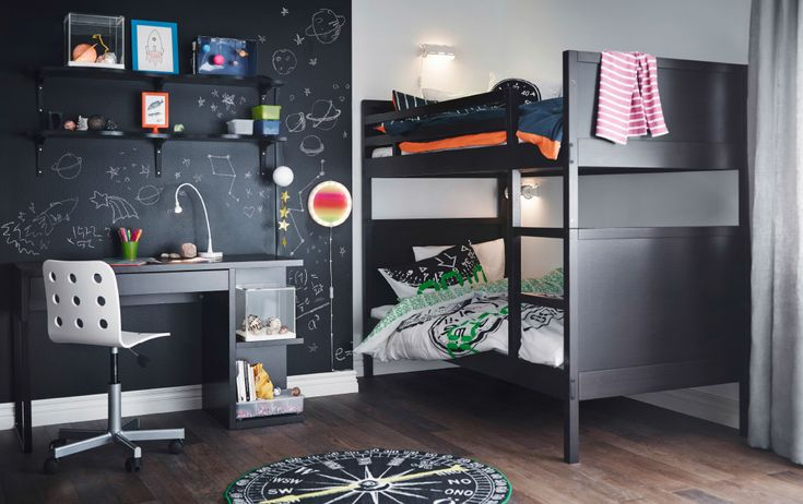 A teenage room with a black bunk bed, desk and wall shelves. Combined with a white swivel chair.
