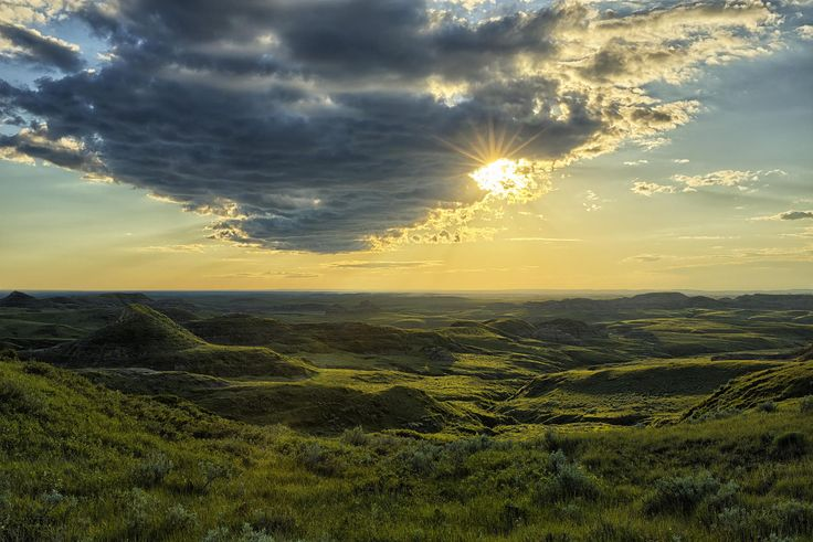 The sun peeks out from behind the clouds and lights up the Killdeer Badlands in the east block of Grasslands National Park, Saskatchewan.