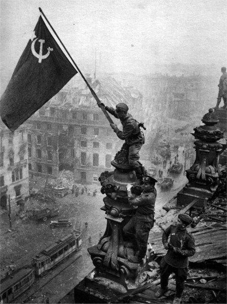 1945, Berlin. Soldado del ejercito rojo, levanta la bandera de la Unión Soviética tras el dominio de la capital alemana. WW2.