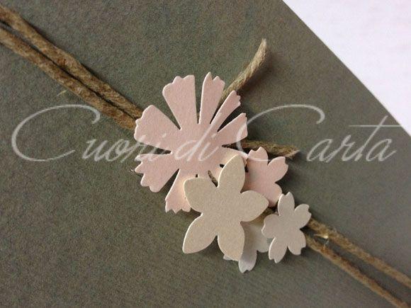 Partecipazione realizzata e scritta a mano con carta millerighe color grigio/salvia, decorata con corda e deliziosi fiorellini in varie tonalità