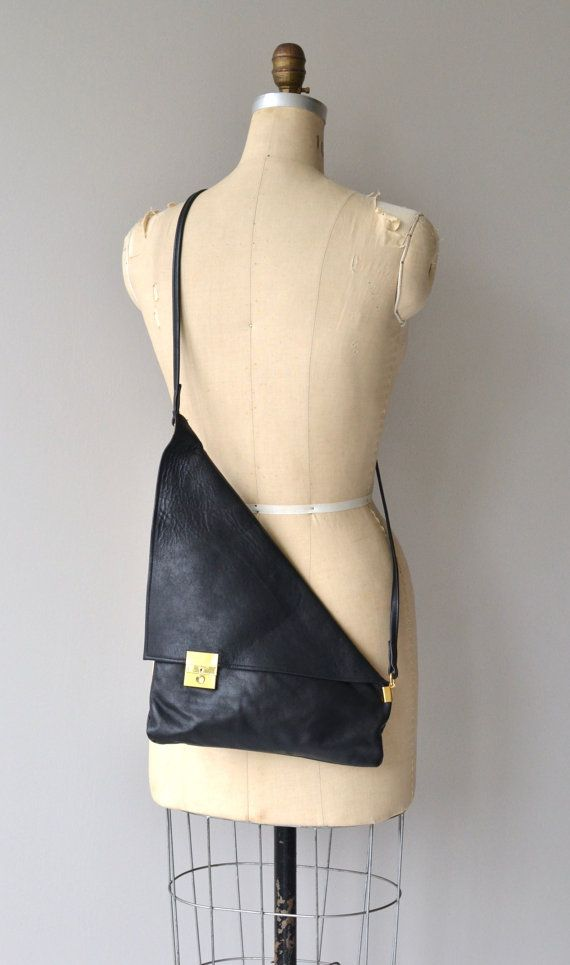 Very cool vintage 1980s soft black leather shoulder bag in uneven triangle shape with brass lock closure, large flap, inner zip pocket and long,