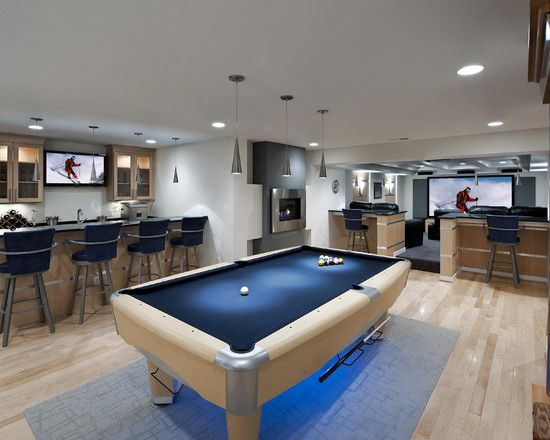 All-purpose basement = perfect man cave. I'd go with a lot more traditional design but you have your bar and seating, pool table, and theater in one. Perfect!