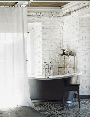 Protagonista en el espacio destinado al dormitorio, la preciosa bañera exenta de aire vintage, de The Water Monopoly, destaca junto a las paredes de ladrillo pintadas de blanco... La rodea una cortina blanca que otorga intimidad.