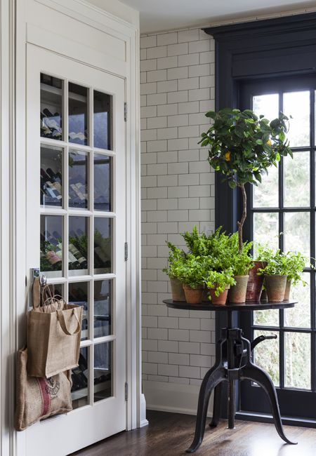 Who says you can't have a little fun with trim color? This room perfectly details how to mix and match with color! The stark white wine room door outlined with matching white finishings flawlessly compliments the black patio door lined with a matte black architrave and casing.  #interiortrim #frenchdoors #inspiration #blackandwhite #interiorfinishings #moulding