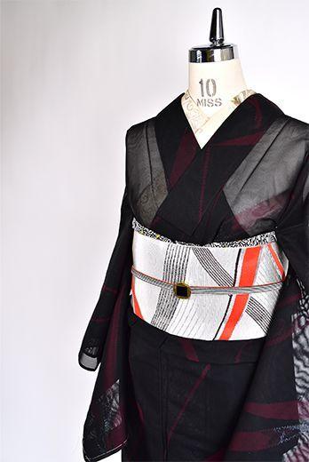 裏地の艶やかな赤を透かす黒地に、葉のモチーフが装飾的にアレンジされたアラベスク模様が浮かび上がる涼やかな紗の夏着物です。