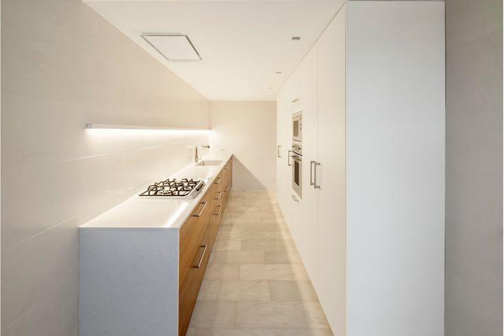 lange, smalle witte keuken met houten kastjes