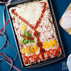 Host a fun family dinner during the holiday season and serve this adorable Ugly Sweater Pizza as the centerpiece. Who needs turkey or prime rib for Christmas dinner when you can have pizza?