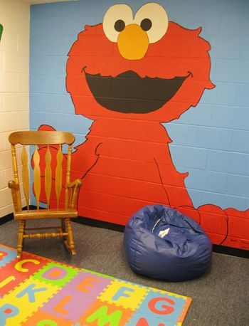 The visitation room at Santa Maria Juvenile Hall for the Baby Elmo program offers a warm welcome for parents and children, with brightly colored toys, a floor mat of alphabet letters and a floor-to-ceiling wall painting of 'Sesame Street's' Elmo.
