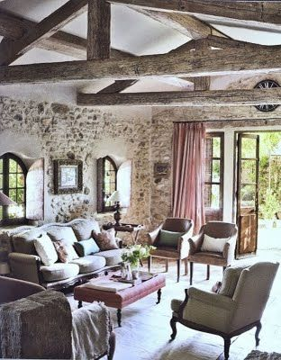 The beams, the stone walls and a cozy sofa. Look at those french doors. Oh my !