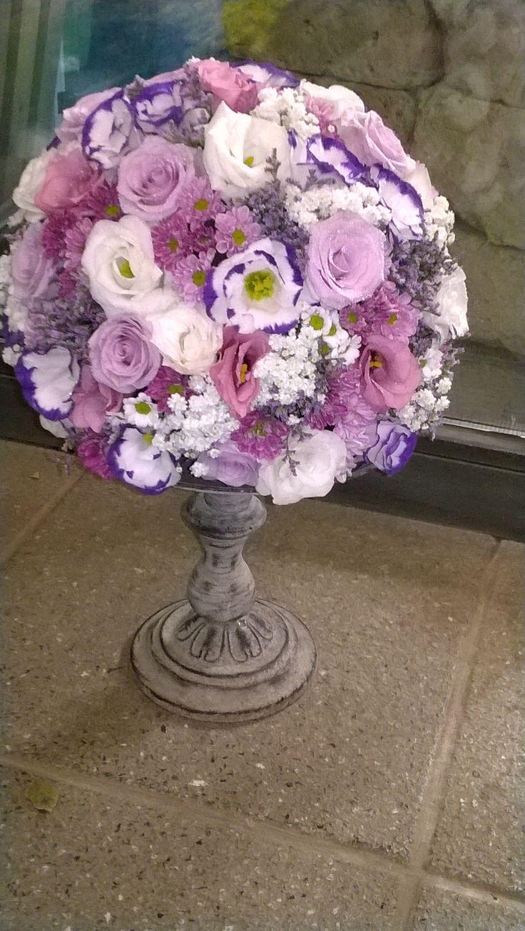 Centrotavola di fiori misti a sfera su alzata di ferro invecchiato.