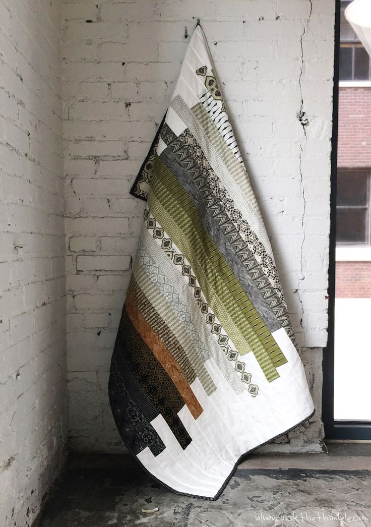 DIY striped strip quilt with a modern design and simple pattern. Muted tones and graphic patterns make this perfect for a man.