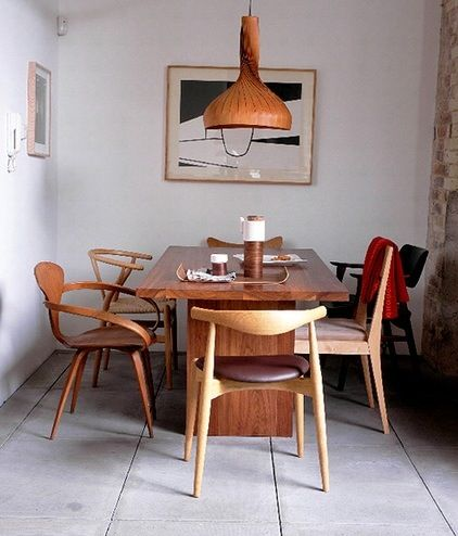 Here's proof that not everything needs to match: six different midcentury chair designs, in various types of wood, create a compelling dining tableau.