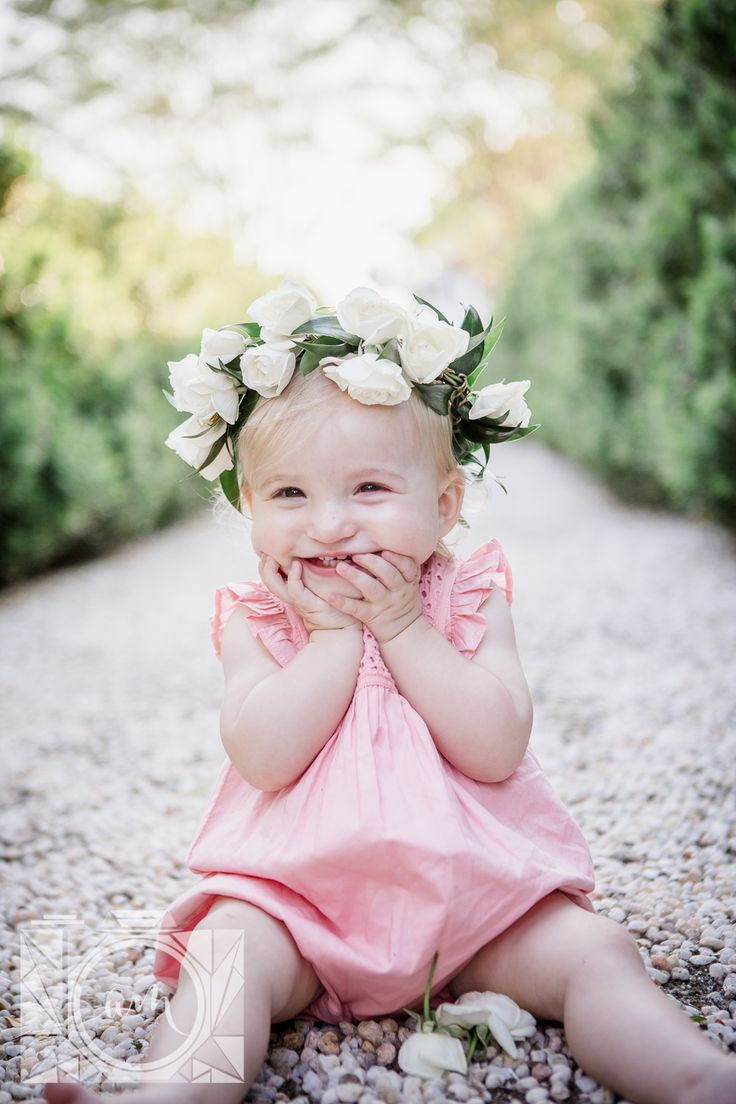 Little one year old girl with a flower crown on with her hands tucked up on her mouth smiling at her 1 year old session at Baxter Gardens by Knoxville Wedding Photographer, Amanda May Photos.