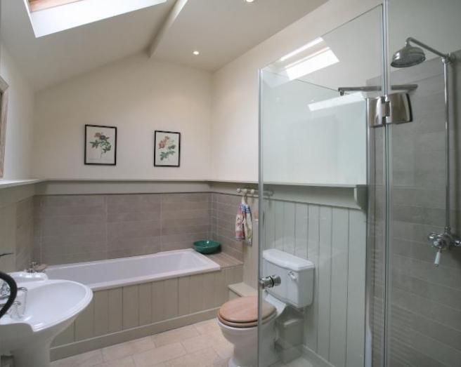 photo of natural beige white bathroom with panelled bath rectangular tiles wood panelling