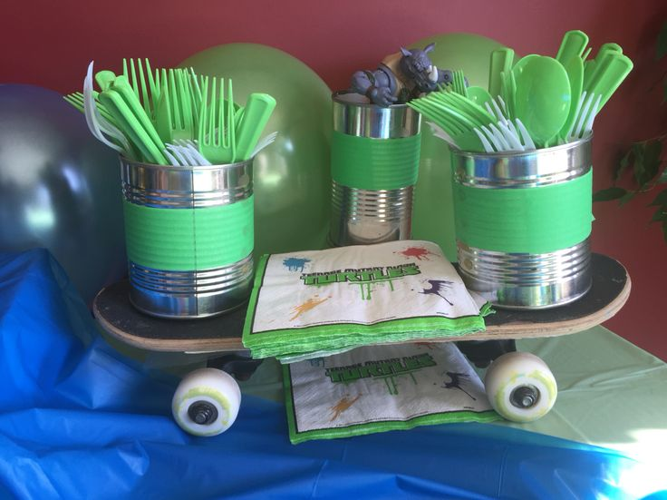 TMNT PARTY - skateboard holding napkins and forks. Metal tins with green tape holding forks