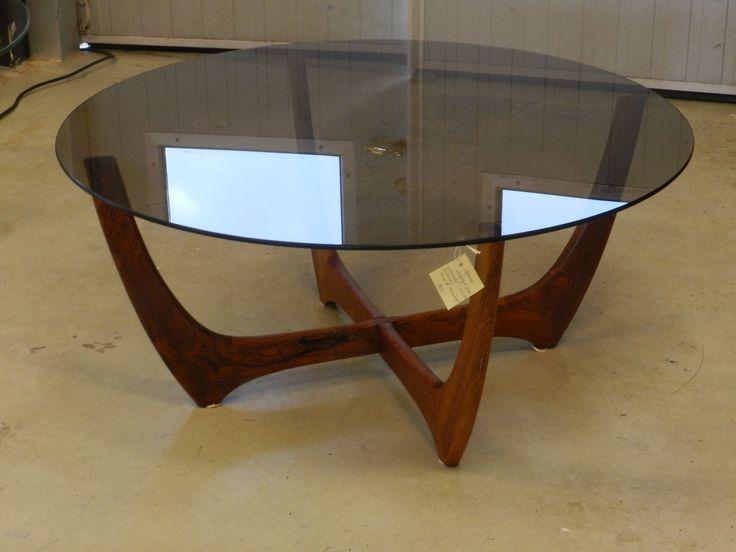 Runt soffbord i rökfärgat glas samt korsad benställning i jakaranda/palisander. 99 cm i diameter samt 44 cm hög. I need this!