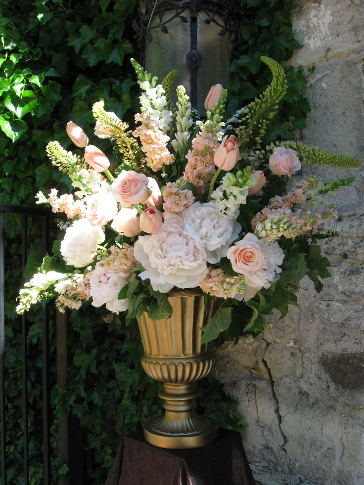 Ceremony Decor: A large urn arrangement in soft pinks, peachy blushes and soft pinks: Peonies, Tulips, Roses, Stock, Tuberose, Eremurus.