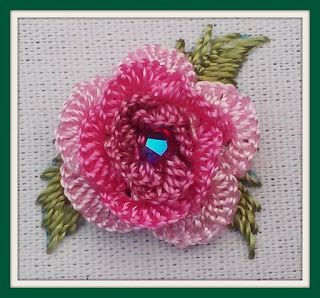 "Canada's Rose: basically 3 rounds with 1st round of stitches through fabric only --5 running cast-on stitches for each round. This version has 15, 15 and 18, changing the color each time around. I added a 4mm Swarovski bicone crystal (the AB finish adds the extra sparkle; the color is named ""Siam"""