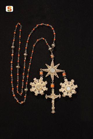 Rosario in filigrana d'argento e vaghi in corallo. Medaglioni teche portareliquie con pietre incluse e crocefisso pendente