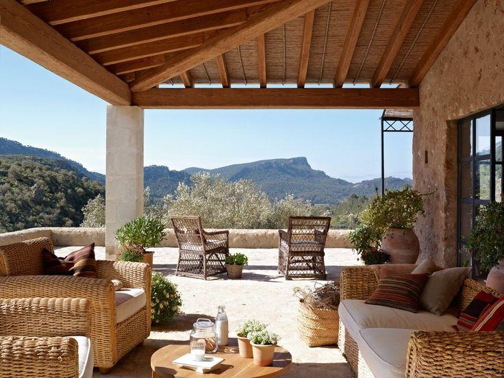 Mirador al paisaje  Las montañas ofrecen al porche su mágico espectáculo. Las butacas de mimbre son de Janer Decoración.