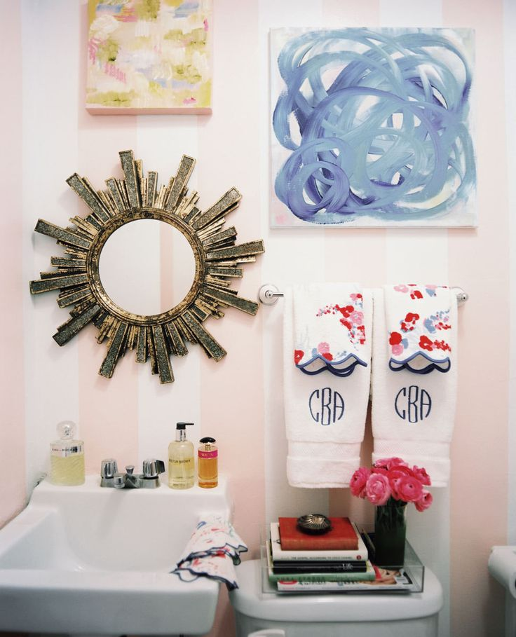 In the bathroom, pink-and-white striped walls and monogrammed linens bring about a feminie flair.