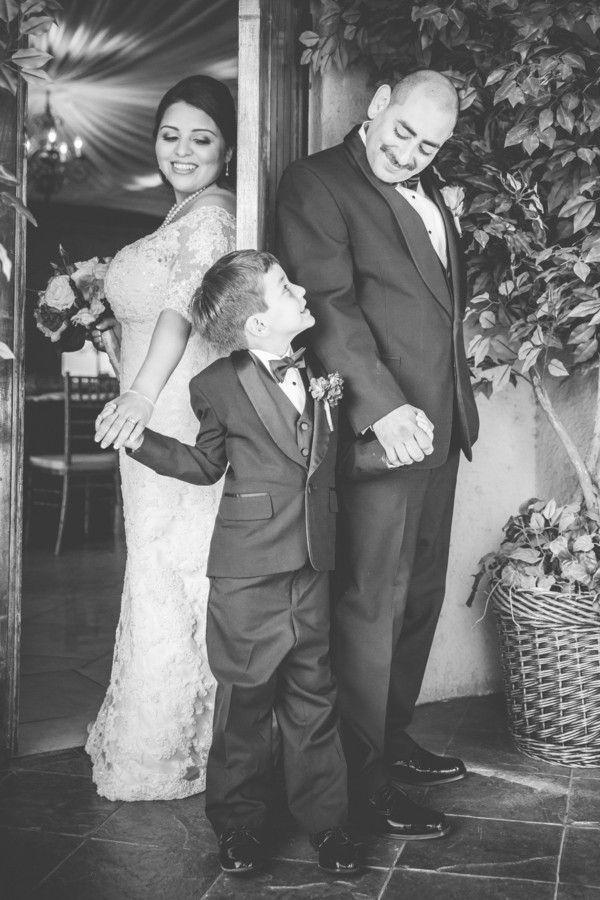 bride and groom look down at son in tuxedo @myweddingdotcom
