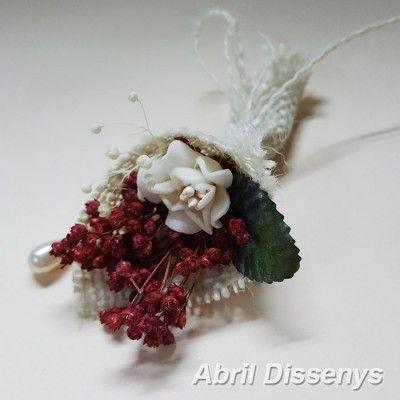 Un alfiler de boda en forma de bouquet de flores secas, envuelto con yute blanco y alfiler de perla, se sirven surtidos de colores