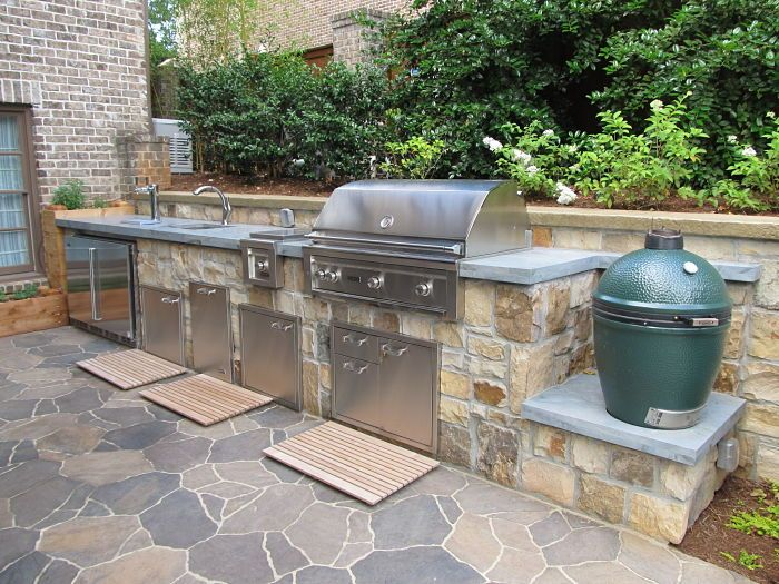 A custom made outdoor kitchen with Lynx appliances (refrigerator, keg cooler, sink, and cooktop), a Lynx grill, and a Big Green Egg smoker.