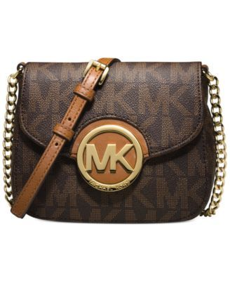 Small in size, big on style. This petite powerhouse from Michael Michael Kors lends a luxe look to your on-the-go accessorizing. Logo-splashed with rich leather trim, a gleaming Mk medallion plaque le