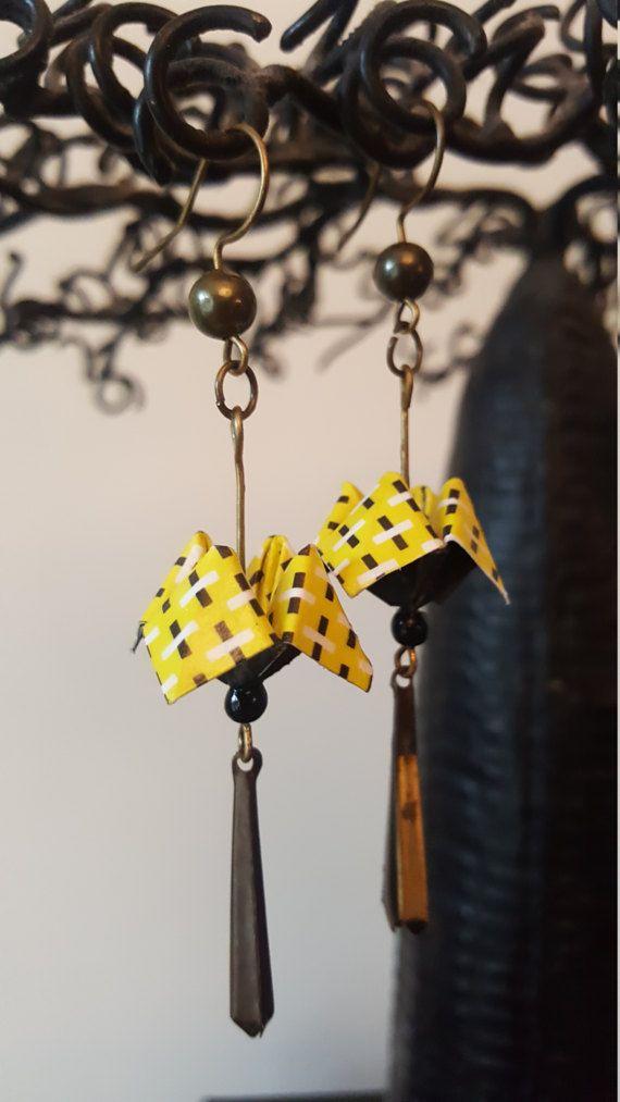 Ces boucles doreilles origami représentent des cocottes réalisées avec du papier. Elles sont de couleur jaune aves des points noirs, montées avec un petit accessoire et des crochets couleur bronze. Les bijoux origami sont légers, féminins, et réalisés avec soin. Les cocottes mesurent 1,5 cm de haut. Elles sont vernies afin dêtre rigides et solides tout en conservant leur légèreté.