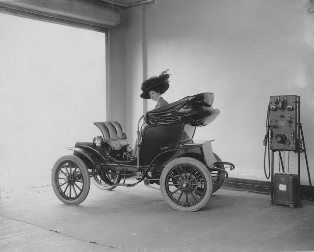A lady sitting on an electric car at the charging station, 1912